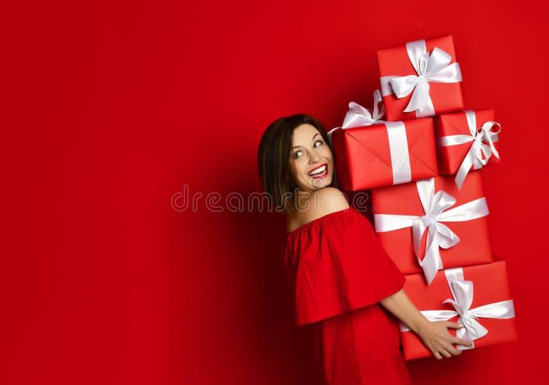 Blithesome födelsedagflicka i klänningen som poserar med gåvor royaltyfria foton