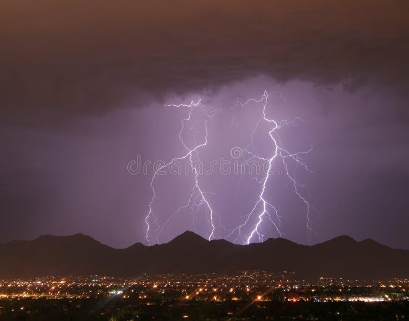 Blitz über der Stadt und den Bergen stockbilder