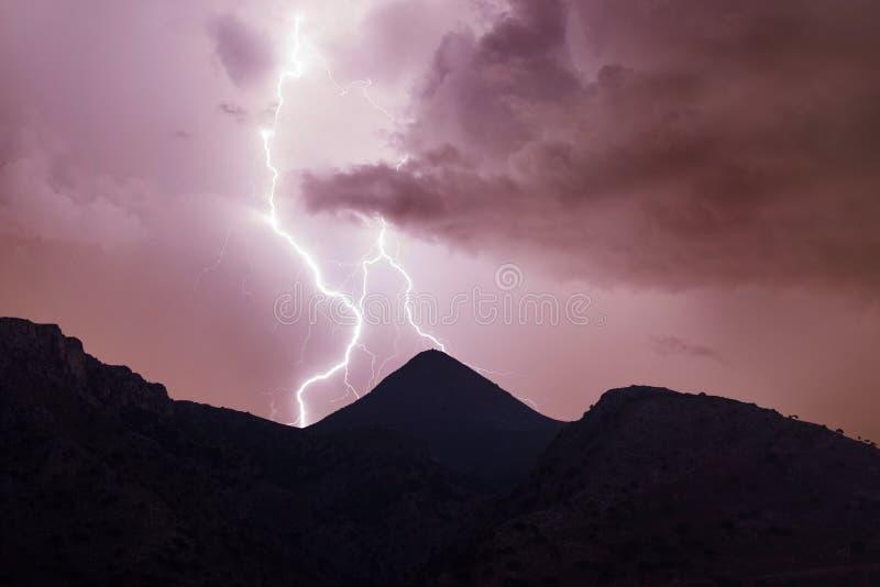 Blitzschlag auf dem Nachtroten bewölkten Himmel in den Bergen lizenzfreie stockbilder