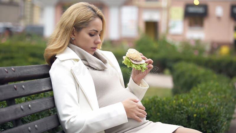 Blivande modern som äter skadligt hamburgaresammanträde, parkerar, högt - fet näring, skräpmat arkivfoto