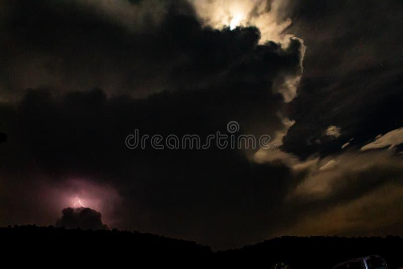 Blixt bak berget på natten royaltyfri fotografi