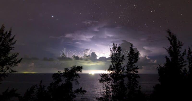 Blixt bak moln med stjärnklar himmel royaltyfri bild