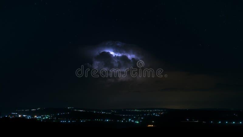 Blixt från ett moln, ovanför en stad, med himmel som är full av stjärnor royaltyfri foto