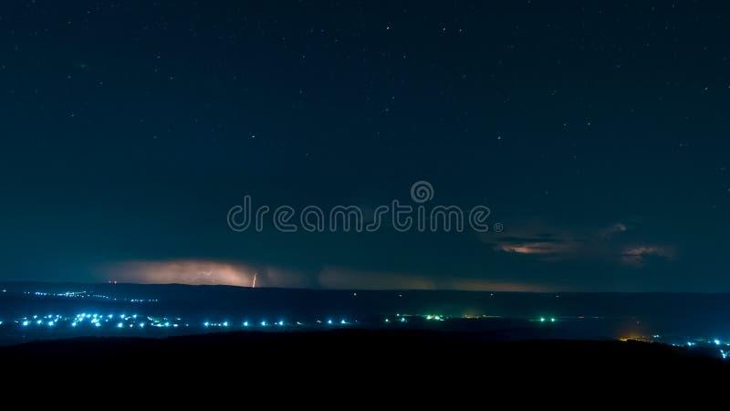 Blixt på en nattlig bakgrund som är full av stjärnor arkivfoton