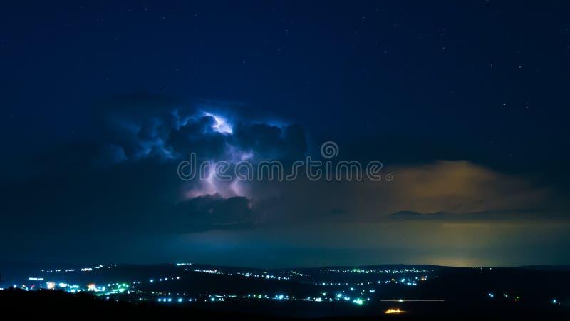 Blixt på en nattlig bakgrund som är full av stjärnor royaltyfri foto