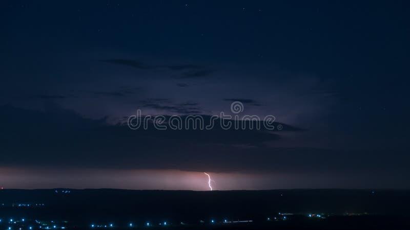 Blixt på en nattlig bakgrund som är full av stjärnor arkivbilder