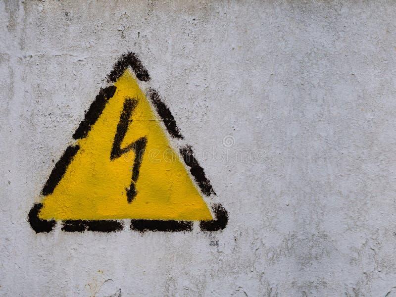 Blixtlåset undertecknar in den gula triangeln på den gemensamma väggen royaltyfri bild