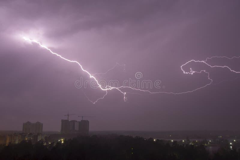Blixtslag över stad i natt thunderstorm royaltyfri bild