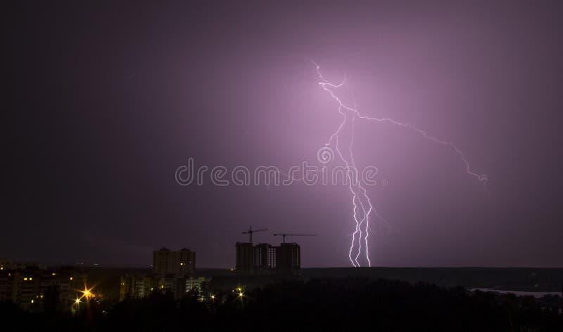 Blixtslag över stad i natt thunderstorm arkivfoto