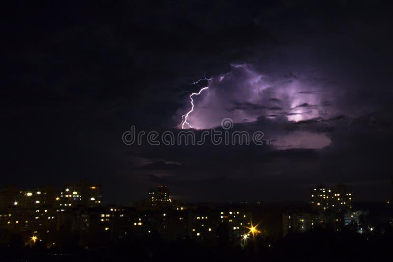 Blixtslag över stad i natt thunderstorm fotografering för bildbyråer