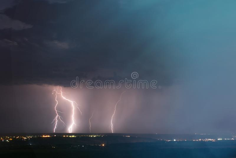 Blixtstorm ?ver stad m?rk blixtnatt f?r bl? stad ?ver skyslag arkivfoto