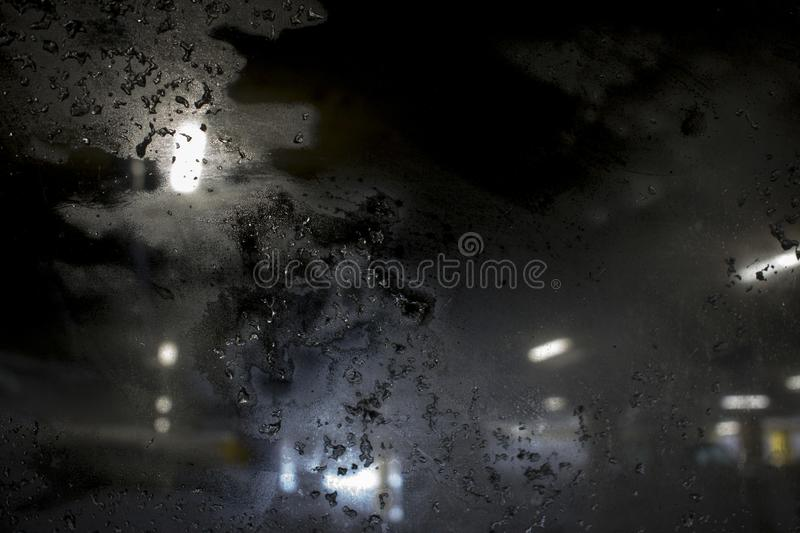 Blizzard on the evening city street against frosted window royalty free stock photography