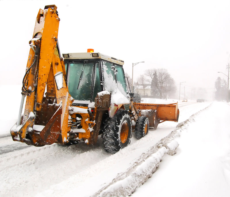 Blizzards sweep through southern Ontario. A snowplow clearing a road stock image