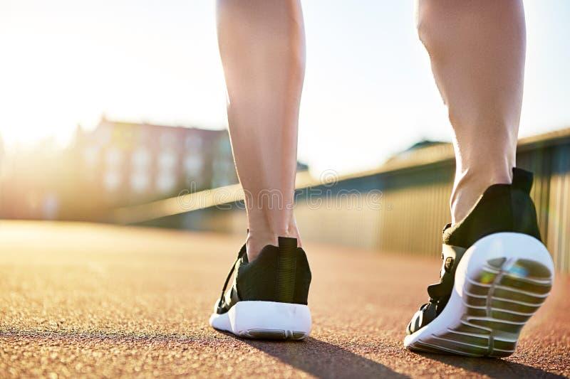 Bloße Beine in den Laufschuhen, die sich vorbereiten zu trainieren stockfotos
