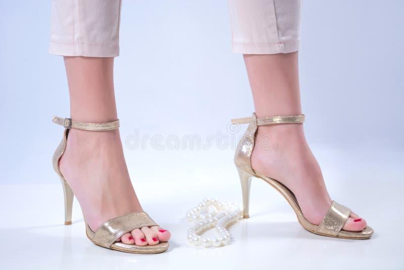Bloße Füße des jungen Mädchens in den goldenen hohen Absätzen und in der Perlenhalskette auf weißem Hintergrund stockfoto