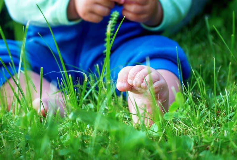 Bloße Füße des kleinen Babys auf frischem grünem Gras stockbild