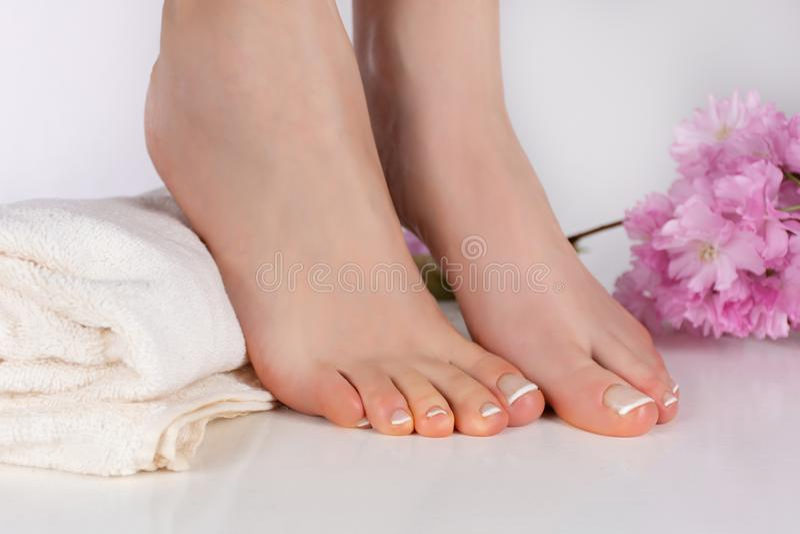 Bloße Füße des Mädchens mit französischer Pediküre auf weißem Tuch und rosa dekorativer Blume in der Schönheit und dem Badekurort lizenzfreie stockfotografie