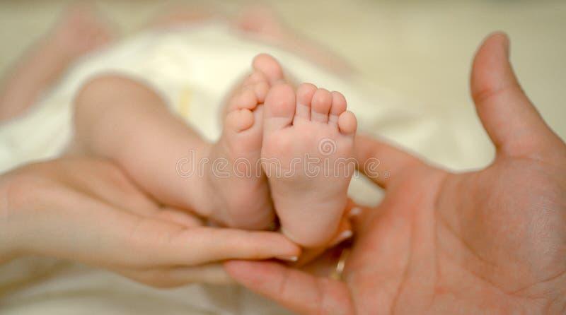 Bloße Füße des neugeborenen Babys des Mutter- und Vatergriffs Kleine Füße in der Frauenhand Gem?tlicher Morgen zu Hause Liebes- u stockfotos