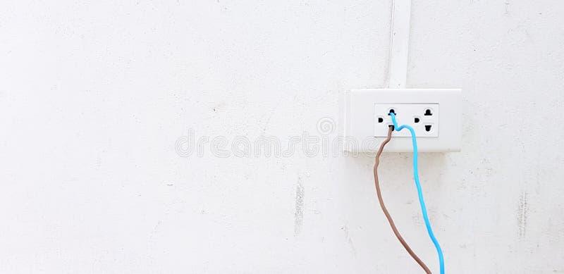 Bloßer blauer und brauner Draht zum Steckdosekasten auf Weißzementwand installieren und anschließen lizenzfreie stockfotografie