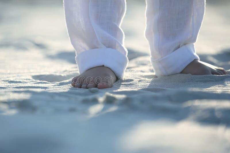 Blo?e F??e eines Kindes in den wei?en Hosen auf dem Sand lizenzfreie stockfotos