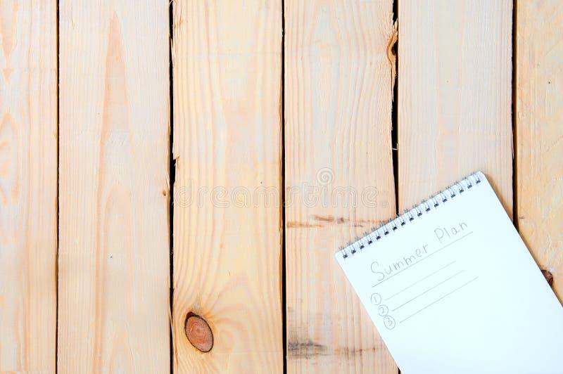 Bloc de notas con entradas para los planes de verano sobre un fondo de madera fotografía de archivo