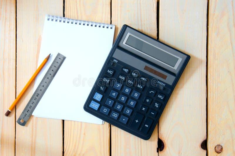 Bloc de notas para entradas con una calculadora. lápiz y regla sobre una mesa de madera fotografía de archivo libre de regalías