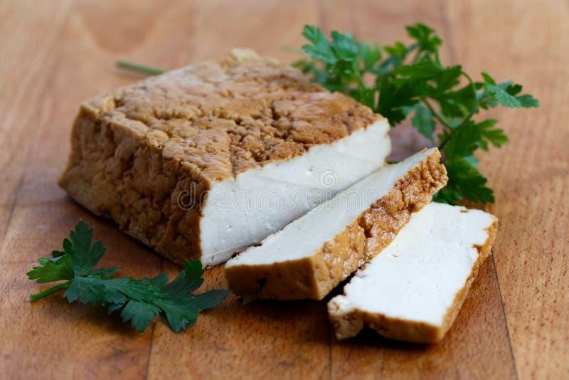 Bloc de tofu fumé, de deux tranches de tofu et de persil frais sur le bois photographie stock libre de droits