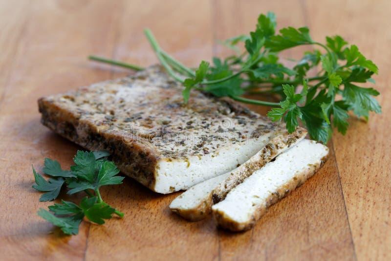 Bloc de tofu mariné avec des herbes, deux tranches de tofu et PA fraîche images libres de droits