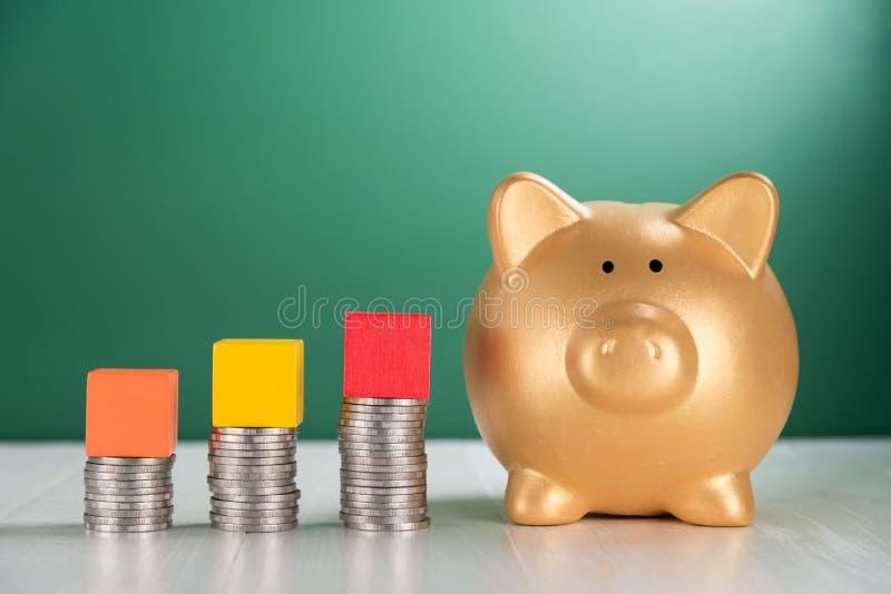 Bloc en bois de cube sur la pile croissante de pièces de monnaie et la tirelire image stock