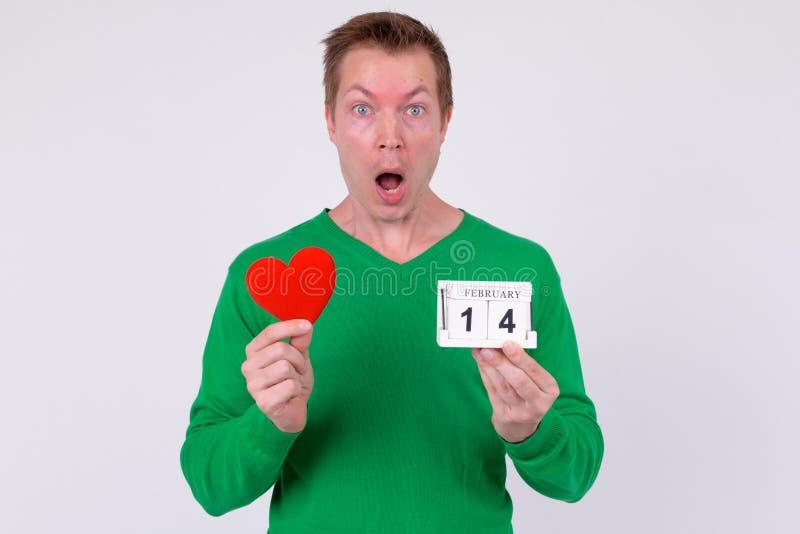 Bloc et coeur de calendrier choqué de participation de jeune homme prêts pour la Saint-Valentin image stock