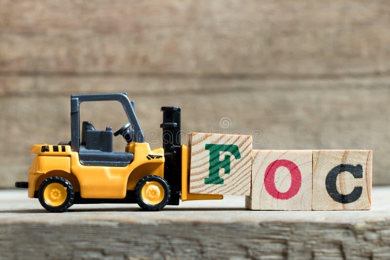 Bloc jaune F de lettre de prise de chariot élévateur de jouet pour accomplir le mot FOC et x28 ; Abréviation de gratuit et de x29 photos libres de droits
