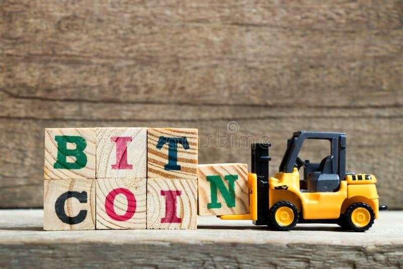 Bloc jaune N de lettre de prise de chariot ?l?vateur de jouet pour accomplir le bitcoin de mot sur le fond en bois images stock