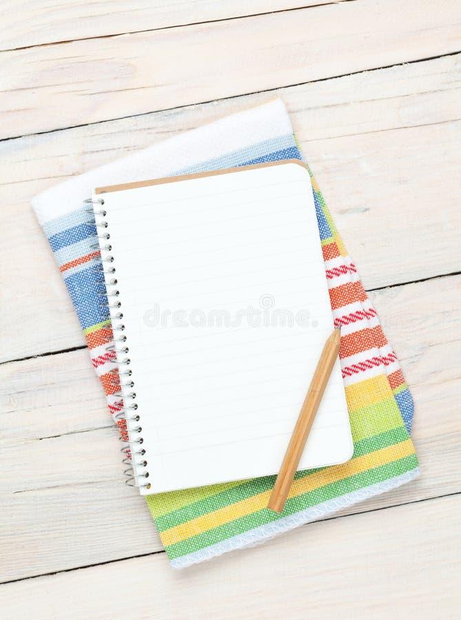 Bloc-notes au-dessus de serviette de cuisine sur la table en bois photos stock