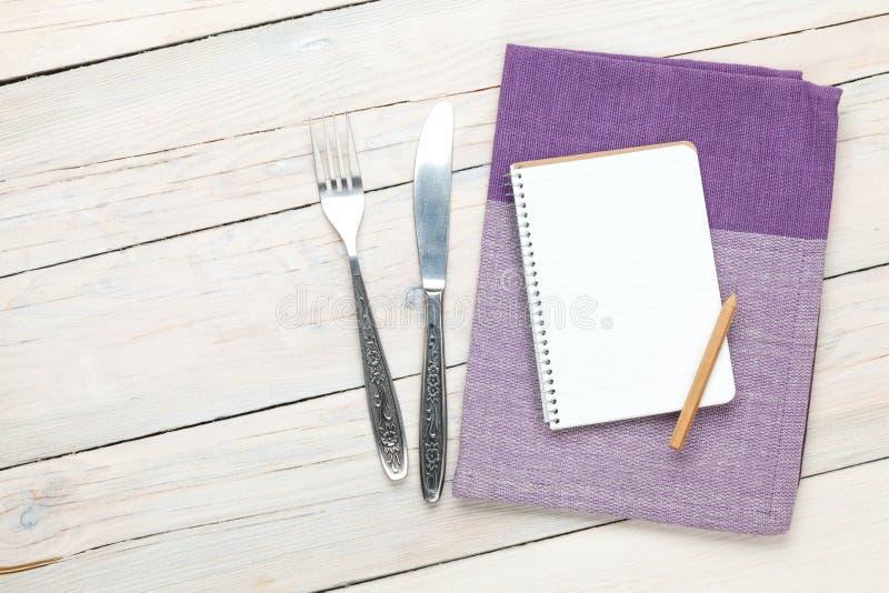 Bloc-notes au-dessus de serviette et d'argenterie de cuisine sur la table en bois images stock