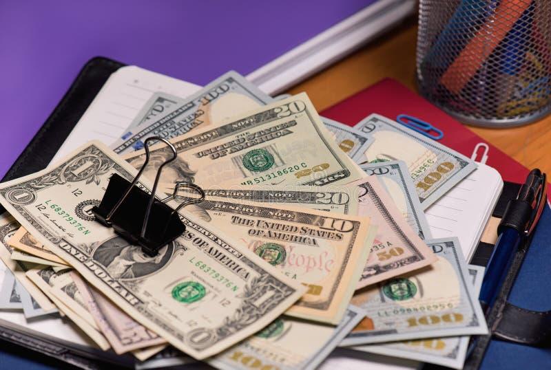 Bloc-notes avec des billets de banque du dollar images stock