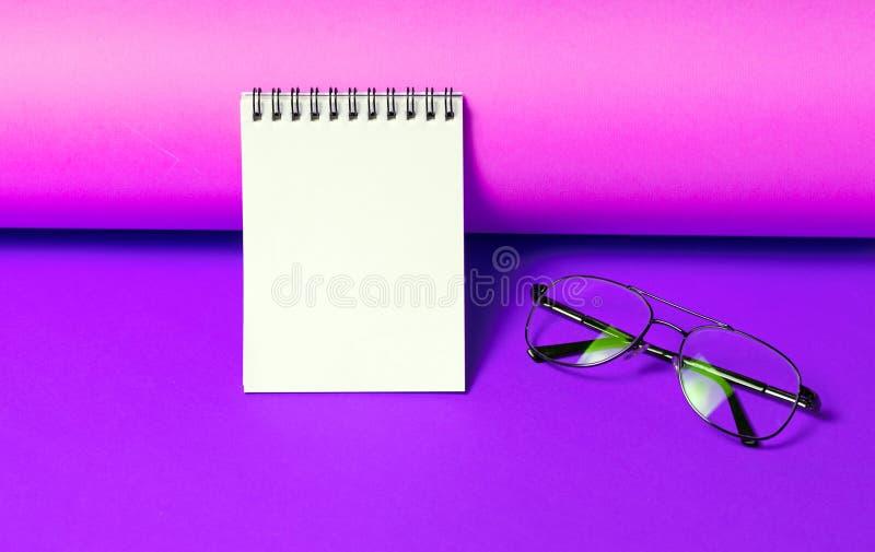 Bloc-notes avec des verres sur le fond pourpre au néon photo stock