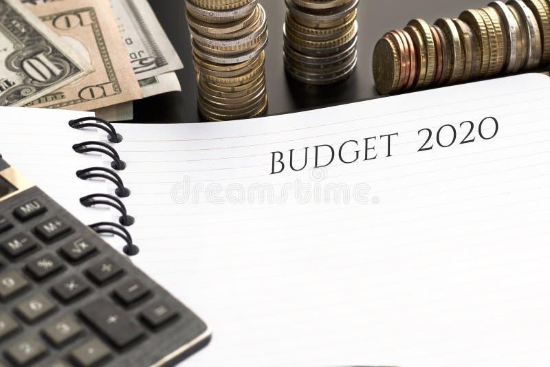 Bloc-notes avec le texte, la calculatrice et l'argent du budget 2020 photo libre de droits
