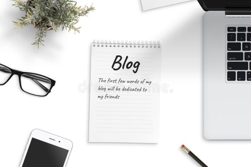 Bloc-notes avec peu de mots du premier blog entouré avec l'ordinateur portable, téléphone intelligent, pencila, usine, verres image libre de droits
