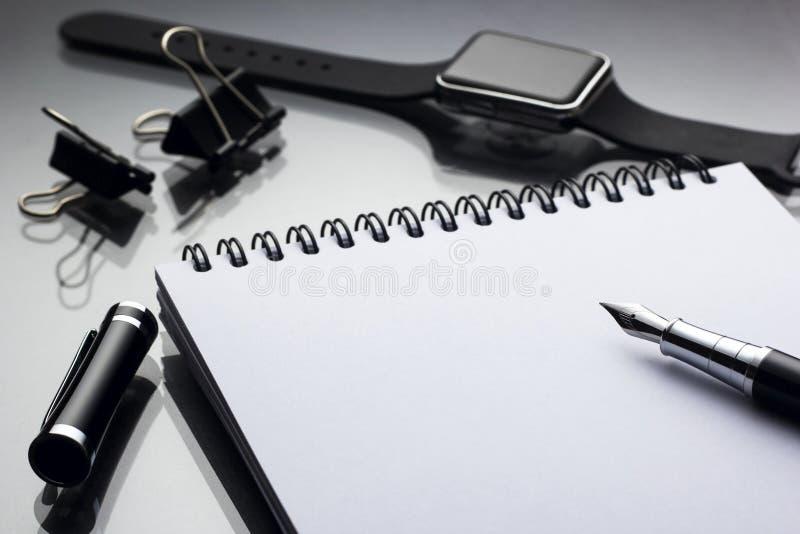 Bloc-notes blanc là-dessus stylo de noir près d'un plan rapproché futé d'horloge sur un gl photos stock