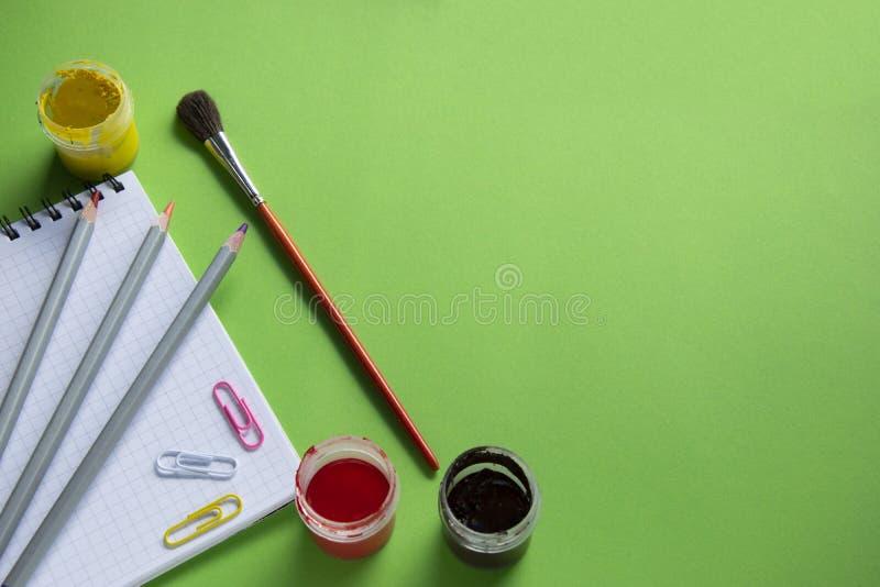Bloc-notes, crayons colorés et brosses, trombones colorés sur un fond vert, de nouveau à l'école image libre de droits
