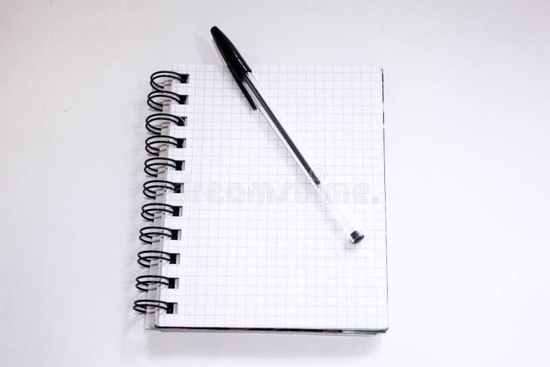 Bloc-notes dans une boîte sur un fond blanc avec un stylo bille noir photographie stock libre de droits