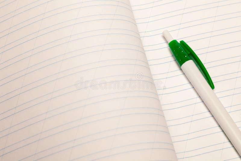 Bloc-notes de plan rapproché et rouler le stylo en plastique avec le livre blanc rayé vide de feuilles L'espace libre clair de co photos libres de droits