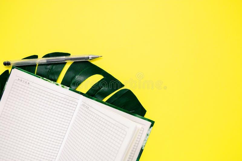 Bloc-notes et stylo blancs pour écrire, feuille de monstera sur le fond jaune, l'espace de copie photographie stock