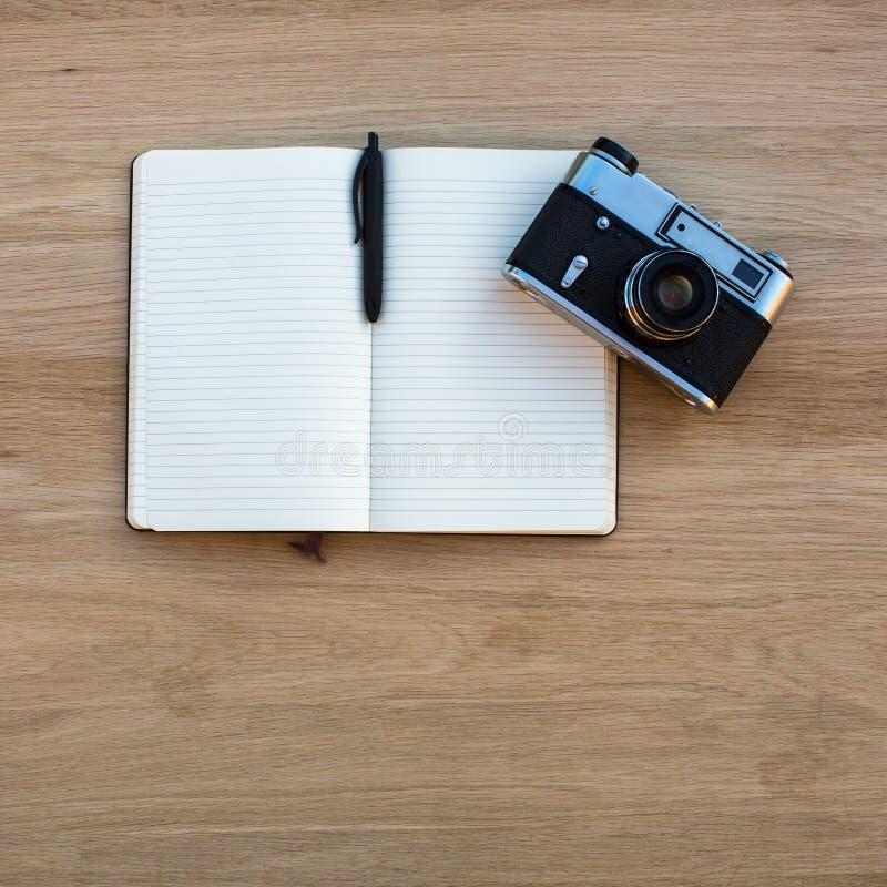 Bloc-notes ouvert avec l'appareil-photo de stylo et de film photos stock