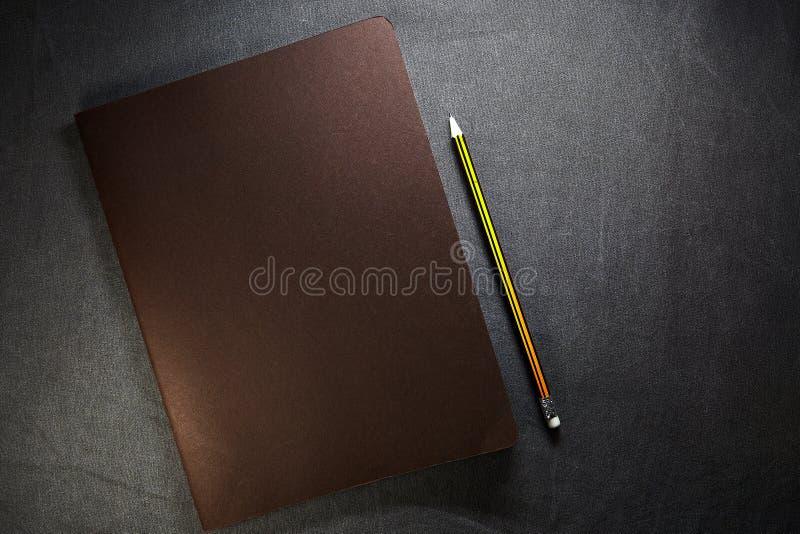 Bloc-notes ouvert de métier avec la couverture en cuir et un crayon gris sur le fond brun images stock