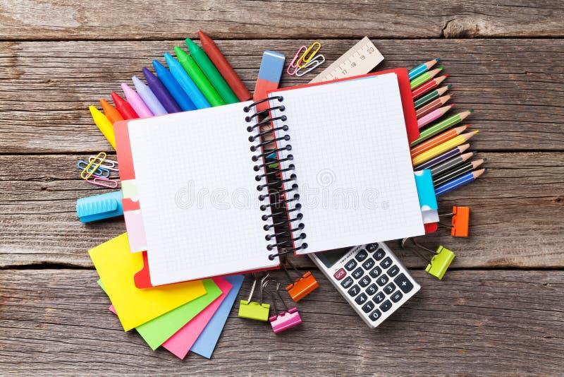 Bloc-notes pour votre texte au-dessus des approvisionnements colorés sur le bois photo libre de droits