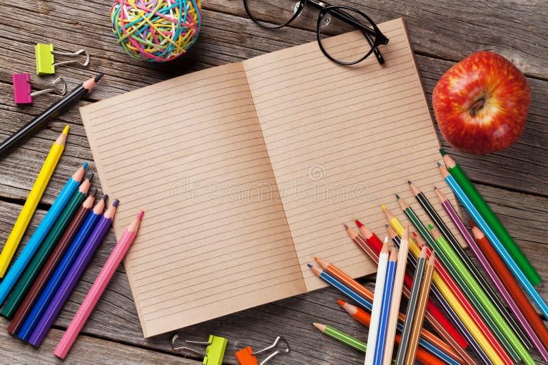 Bloc-notes pour votre texte et approvisionnements colorés au-dessus de bois images stock