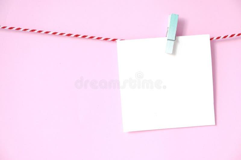Bloc-notes vide de livre blanc accrochant sur le fond rose, avec la copie images libres de droits