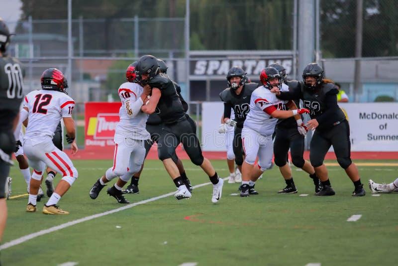 Blocage de joueurs de football de lycée photo libre de droits