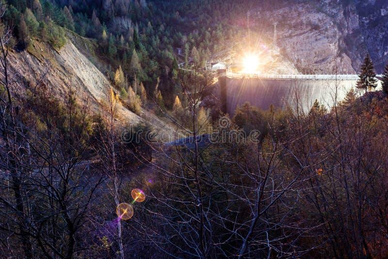 Bloccaggio di notte di una diga nelle alpi fotografia stock